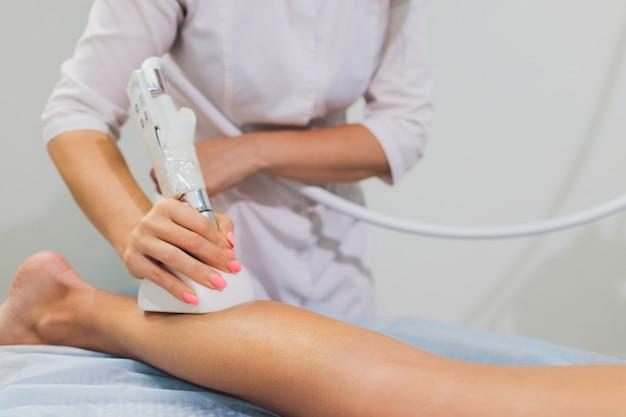 Vista recortada de cosmetologista com rolo fazendo massagem de starvac nádegas.