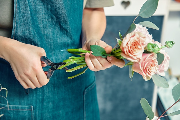 Vista recortada de florista fazendo buquê fresco. fêmea corta flores em pé no balcão. floral, estúdio de decoração. entrega de flores. espaço para o projeto. local de trabalho e conceito profissional