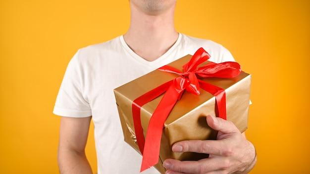 Vista recortada de jovem bonito segurando uma caixa de presente em amarelo