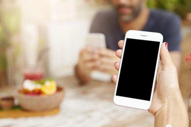 Vista recortada de jovem fêmea usando smartphone touchscreen durante o almoço no café