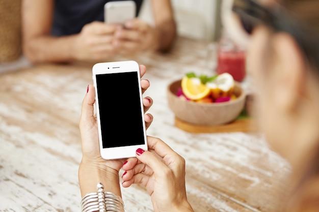 Vista recortada de mãos femininas com manicure vermelha, segurando o telefone celular com tela em branco.
