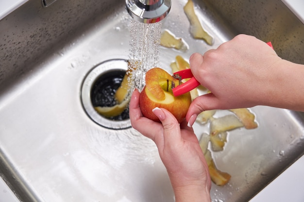 Vista recortada de mãos femininas descascando maçã sobre a máquina de triturador de resíduos alimentares