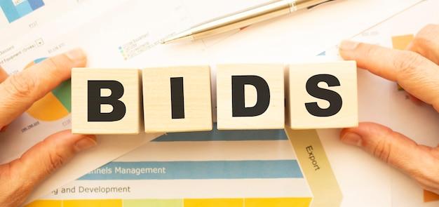 Vista recortada de mãos segurando cubos de madeira com as letras bids na mesa de trabalho
