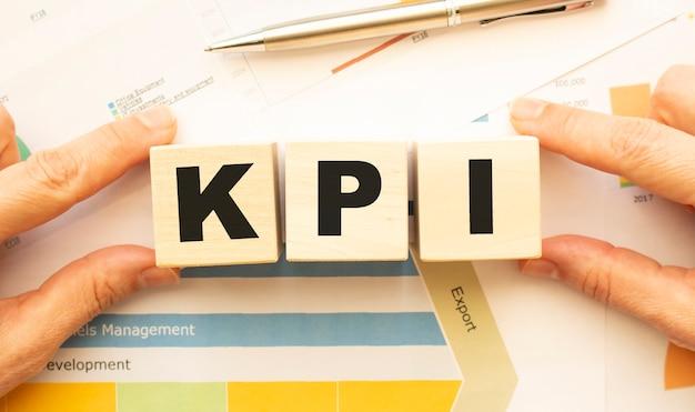 Vista recortada de mãos segurando cubos de madeira com as letras kpi na mesa de trabalho
