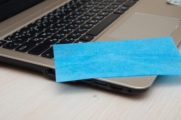 Vista recortada de mulher limpando a tela do laptop com guardanapo perto de cadernos no fundo desfocado na mesa