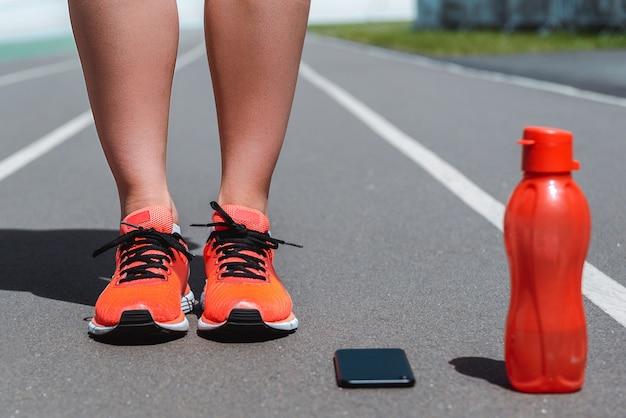 Vista recortada de pernas femininas de tênis na pista de corrida perto de garrafa de smartphone e esporte