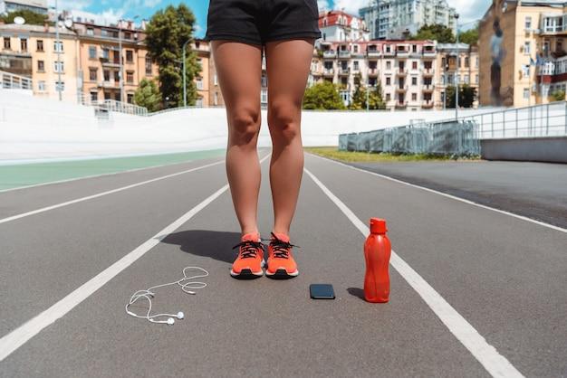 Vista recortada de pernas femininas em tênis na pista de corrida perto de garrafa de smartphone, fones de ouvido e esportes