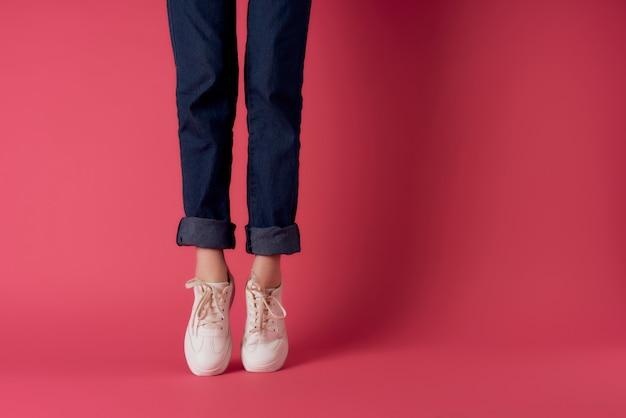 Vista recortada de sapatos femininos posando com fundo rosa