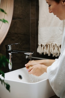 Vista recortada de uma mulher madura de cabelos curtos, lavando as mãos com um bloco de sabão ecológico. ela está parada na frente do espelho em um banheiro.