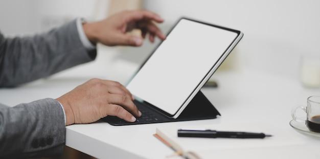 Vista recortada do empresário profissional trabalhando em seu projeto com tablet de tela em branco