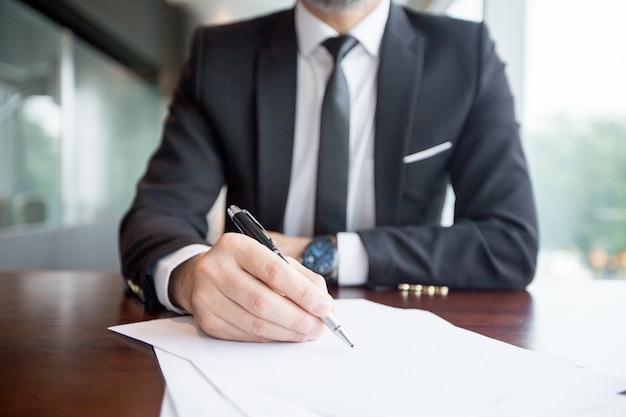 Vista recortada do líder empresarial fazendo anotações
