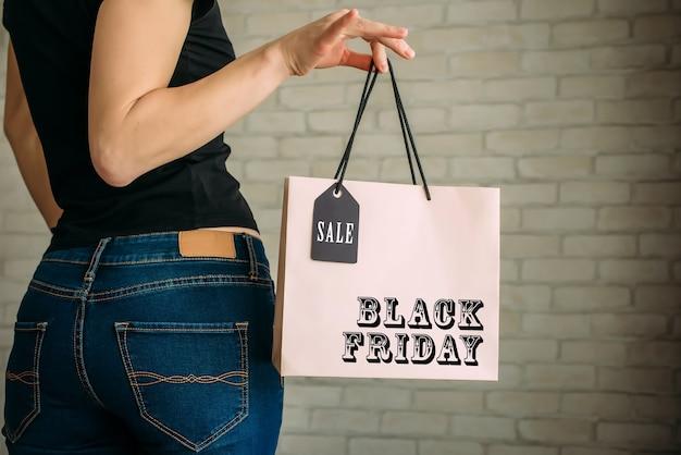 Vista recortada mulher sexy em jeans segurando um saco de papel com etiqueta na mão contra uma parede de tijolos brancos