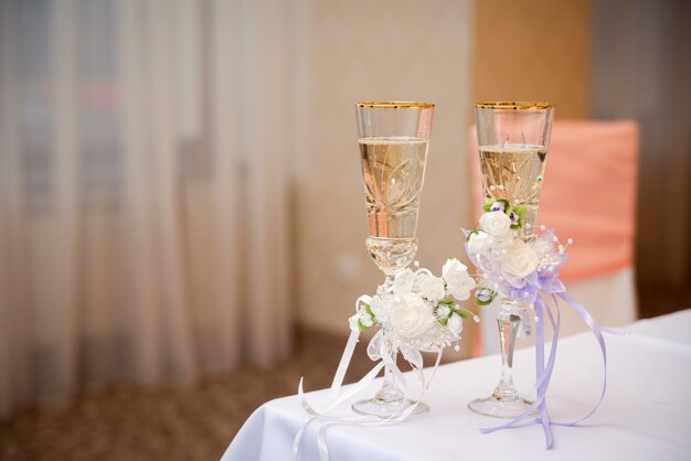 Vista romântica de copos de casamento com champanhe na toalha de mesa branca no restaurante.