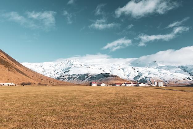 Vista serena do campo marrom com as casas de telhado vermelho e montanhas nevadas no
