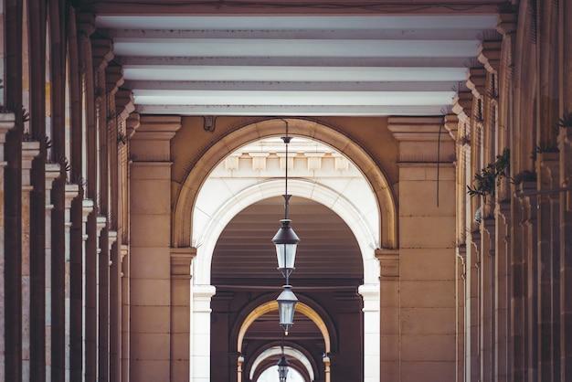 Vista simétrica das passagens com postes de luz e arcadas de vários edifícios neoclássicos