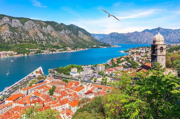 Vista sobre a baía de kotor, a igreja de nossa senhora do remédio e os telhados da cidade velha, montenegro.