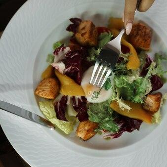 Vista sobre as mãos com talheres e salada de legumes e ovo pochê em um prato branco dentro de casa na mesa. garfo e faca nas mãos da garota. café da manhã saudável