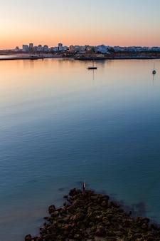 Vista sonhadora da cidade de portimão, no horizonte ao pôr do sol.