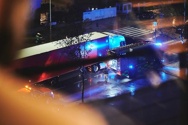 Vista subjetiva por trás de um homem olhando pela janela para um caminhão de bombeiros em uma noite chuvosa