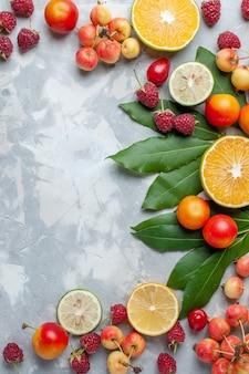 Vista superior à distância, limões e cerejas, frutas frescas em uma mesa branca-clara, frutas frescas maduras
