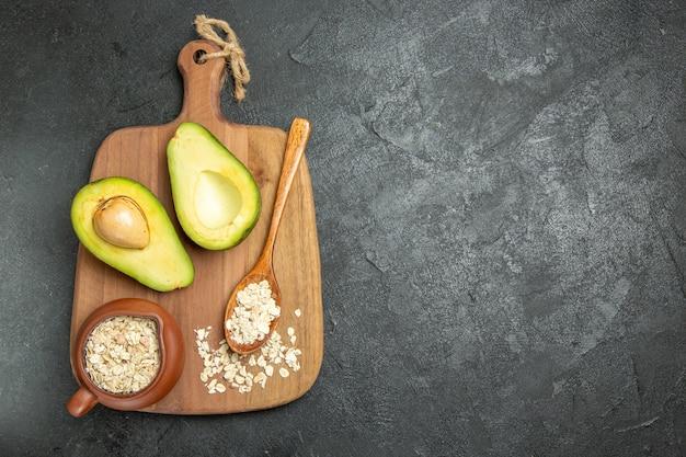 Vista superior abacate fresco com cereais crus no fundo cinza frutas exóticas café da manhã fresco