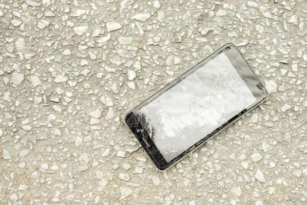 Vista superior acidente celular preto cair para a estrada e vidro quebrado