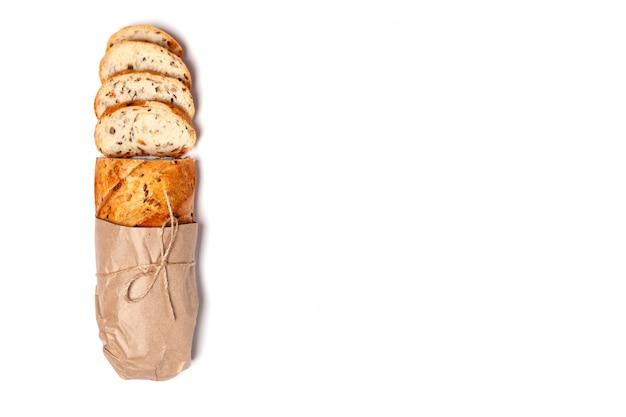 Vista superior acima da composição, pão sem glúten fresco cortado em grão caseiro do trigo em papel ofício amarrado com barbante.