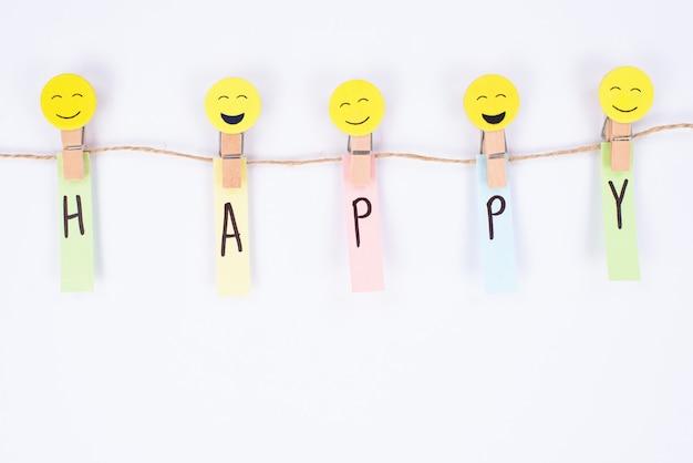 Vista superior acima de um smiley de cor diferente com diversos humores e palavra feliz em adesivos de papel isolados na parede branca
