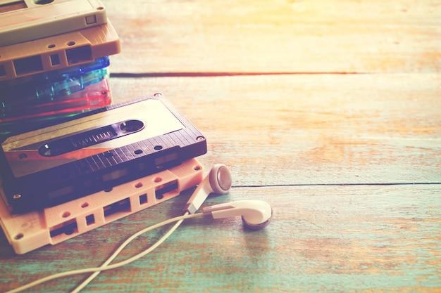 Vista superior (acima) tiro da cassete de fita retro com fone de ouvido na mesa de madeira - estilos de efeito de cor vintage.