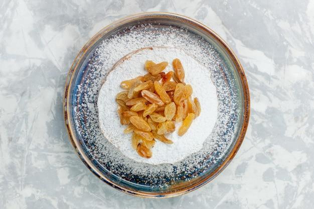 Vista superior, açúcar em pó, passas e uvas secas dentro do prato na mesa branca