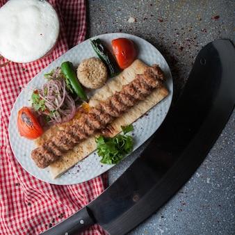 Vista superior adana kebab com faca e legumes fritos e cebola picada e ayran em chapa branca