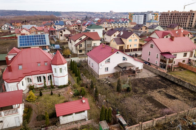 Vista superior aérea da área de subúrbio com belas casas e carros em dia ensolarado.