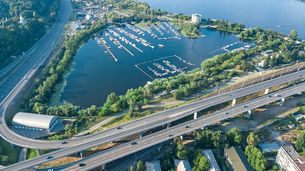 Vista superior aérea da ponte de darnitsky, automóvel e ferrovia, sobre o rio dnieper. skyline do sol da cidade, ucrânia