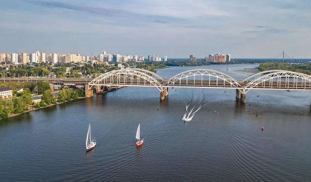 Vista superior aérea da ponte de darnitsky, iates e barcos navegando no rio dnieper