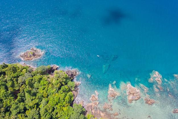 Vista superior aérea das ondas do oceano, praia e litoral rochoso e bela floresta.