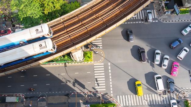 Vista superior aérea de um carro na pista de asfalto e faixa de pedestres na estrada de tráfego.