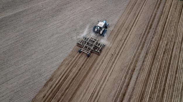 Vista superior aérea de um trator, colheitadeira arando terras agrícolas na primavera