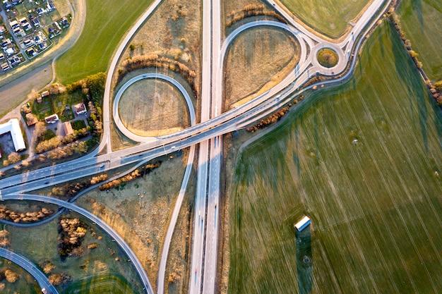 Vista superior aérea do cruzamento de estrada moderna rodovia, telhados de casa em fundo de campo verde primavera. fotografia de zangão.