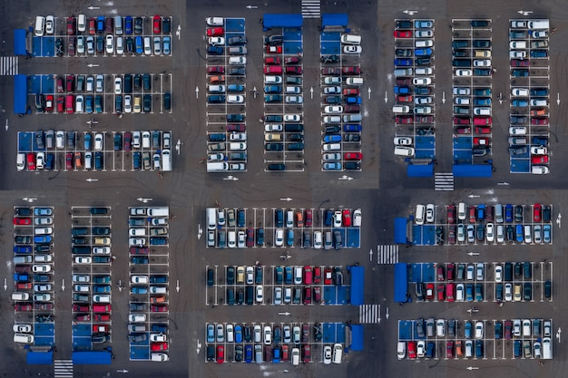 Vista superior aérea do estacionamento com muitos carros. muitos carros estão estacionados em um estacionamento com manchas brancas. lugares de estacionamento com padrão de veículos.