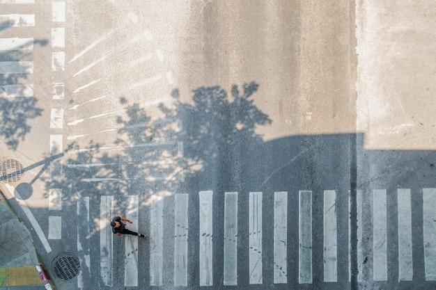 Vista superior aérea do homem andar na rua na cidade ao longo da estrada de tráfego de passagem para pedestres.