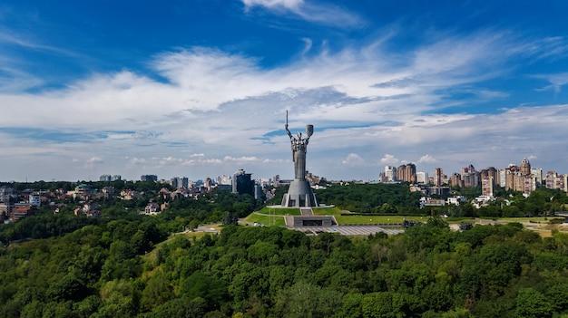 Vista superior aérea do monumento da estátua da pátria de kiev nas colinas de cima e da paisagem urbana, cidade de kiev, ucrânia