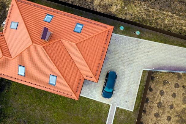 Vista superior aérea do telhado de telha metálica da casa com janelas do sótão e carro preto no quintal pavimentado.