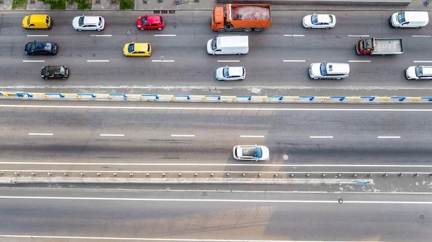 Vista superior aérea do tráfego automóvel de estrada de muitos carros na estrada de cima, o conceito de transporte da cidade