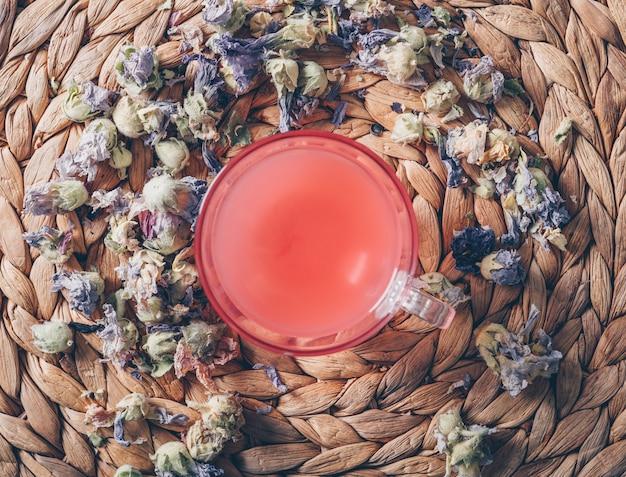 Vista superior água de cor vermelha em fundo trivet com ervas de chá horizontal