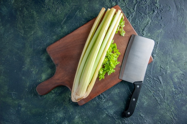 Vista superior aipo verde fresco com uma grande faca em fundo azul escuro salada dieta saudável comida refeição foto colorida