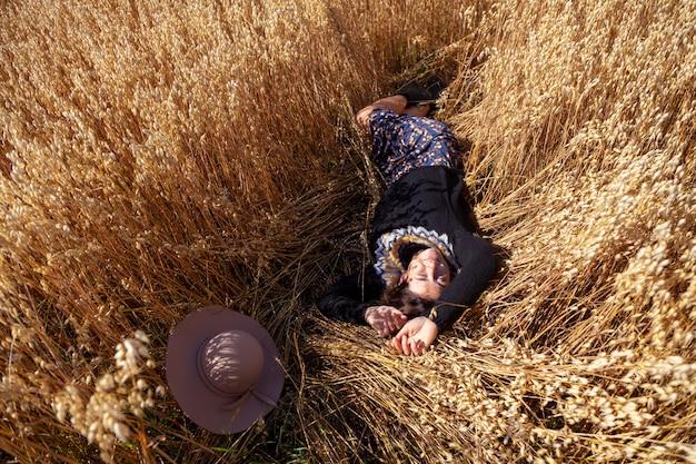 Vista superior alegre mulher feliz em uma linda camisola situa-se num campo de trigo, ao lado de um chapéu com aba larga