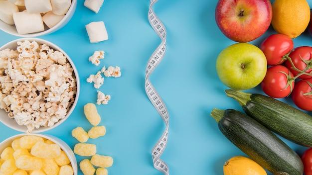 Vista superior alimentos saudáveis vs saudáveis com fita métrica