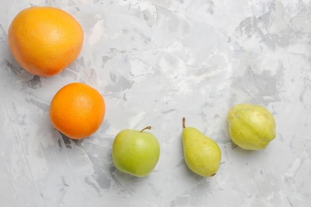 Vista superior alinhada com frutas frescas, peras e tangerinas no fundo branco