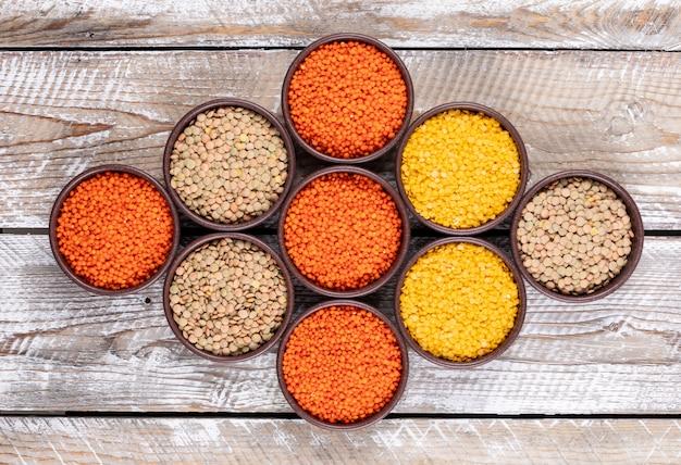 Vista superior alinhadas diferentes lentilhas em tigelas marrons na mesa de madeira bege. horizontal