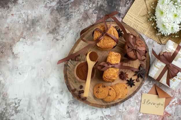 Vista superior amarrada cookies de cacau em uma tigela na placa de madeira carta de amor buquê de flores na mesa